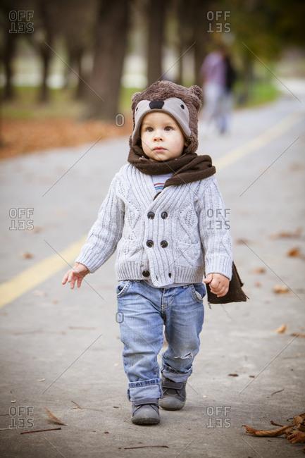 Toddler with cap and scarf walking on a street, Osijek, Croatia