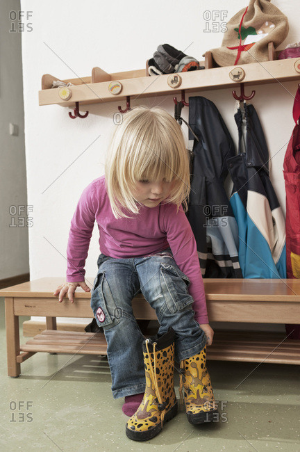 Girl Pulling On Boots, Kottgeisering, Bavaria, Germany, Europe
