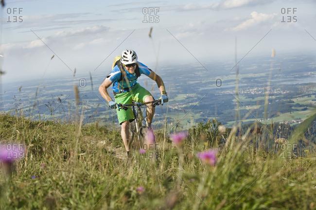 Mountain biker riding on Alpine trail, Samerberg, Germany
