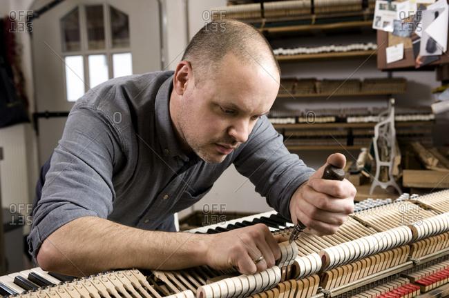 Instrument maker adjusting a piano, Regensburg, Bavaria, Germany