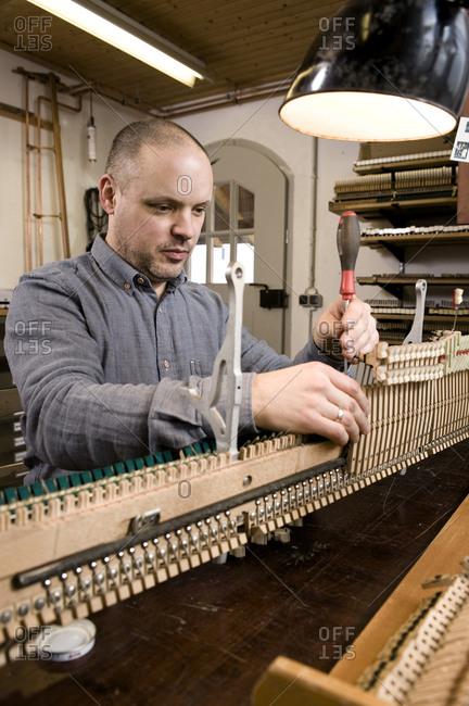 Instrument maker adjusting musical mechanism of a piano, Regensburg, Bavaria, Germany