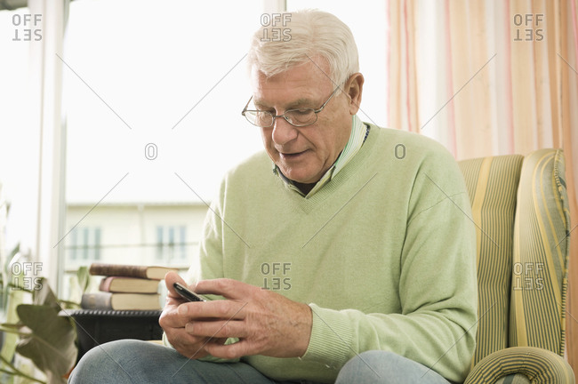 Senior man using phone in nursing home, Bavaria, Germany