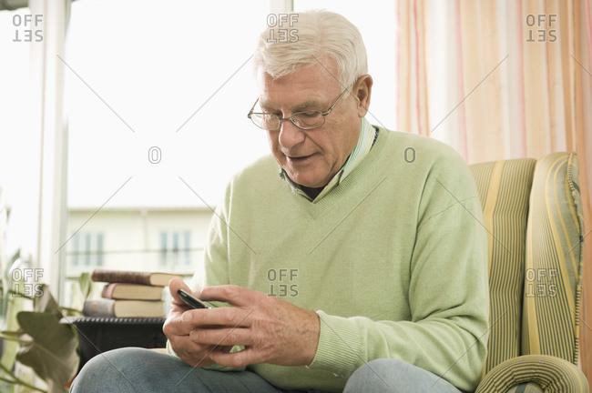 Senior man using phone in nursing home, Bavaria, Germany