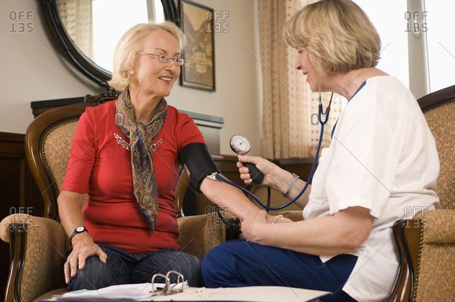 Nurse checks senior woman's blood pressure, Bavaria, Germany