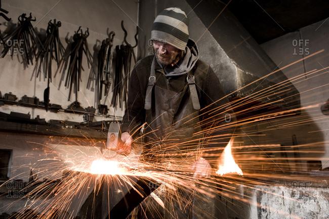 Blacksmith hammering metal on an anvil, Landshut, Bavaria, Germany