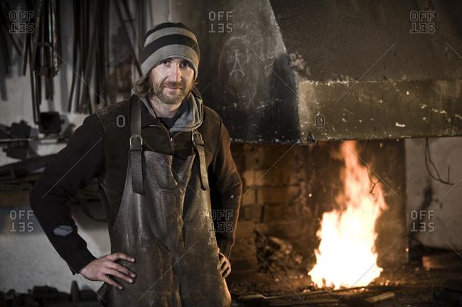 Blacksmith standing in workshop, forge in background, Landshut, Bavaria, Germany