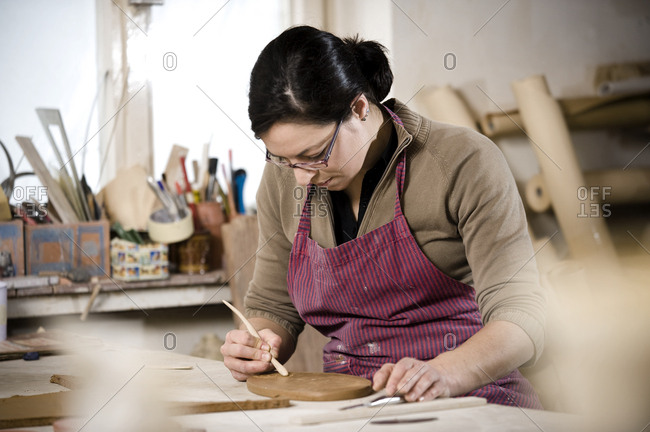 Craftswoman carving pattern into clay, Bavaria, Germany, Europe