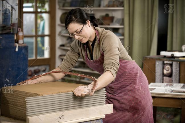 Craftswoman cutting clay in workshop, Bavaria, Germany, Europe