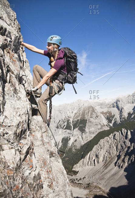 Female alpinist rock climbing, Innsbruck route, Austria