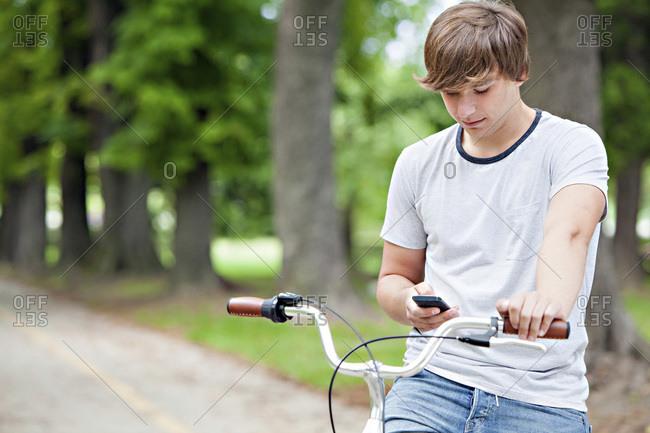 Young man with bicycle using mobile phone, Osijek, Croatia
