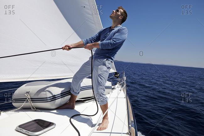 Man on sailboat pulling rope, Dalmatia, Croatia, Europe