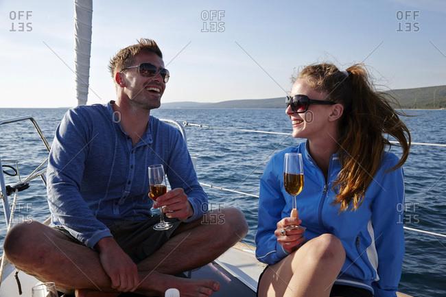 Young couple on sailboat drinking wine, Dalmatia, Croatia, Europe