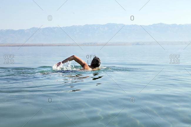 Croatia, Young man swims in the Adriatic Sea
