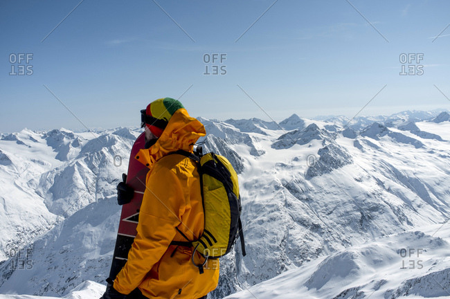 Back country skier taking a look at mountain range, European Alps, Tyrol, Austria