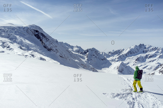 Back country skier looking at mountain scenery, European Alps, Tyrol, Austria
