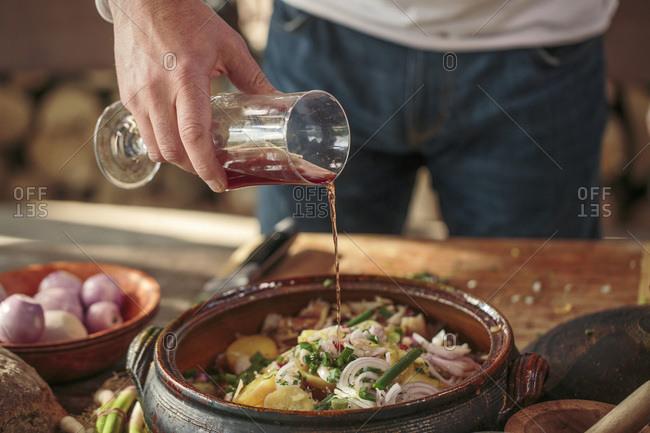 Person preparing potato salad adding sauce