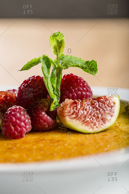 Creme brulee with raspberries and mint, close-up