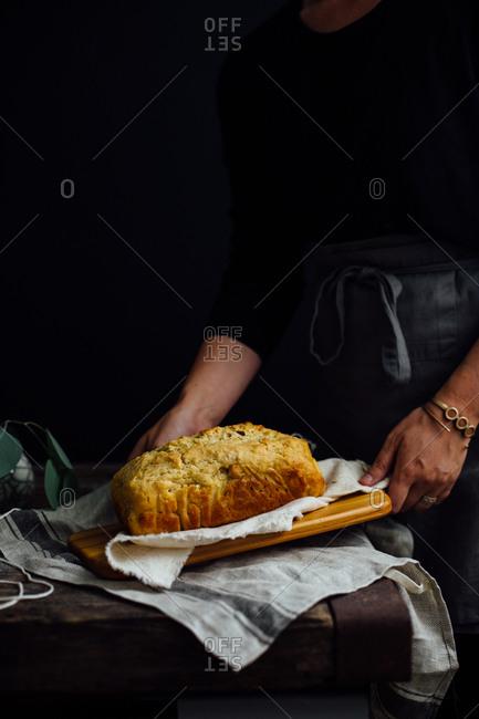 Woman holding bread on wooden board
