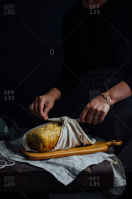 Woman tying towel on bread
