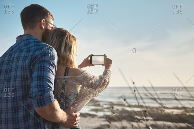 Couple in love on vacation, taking photos of the scenery on their phone creating memories