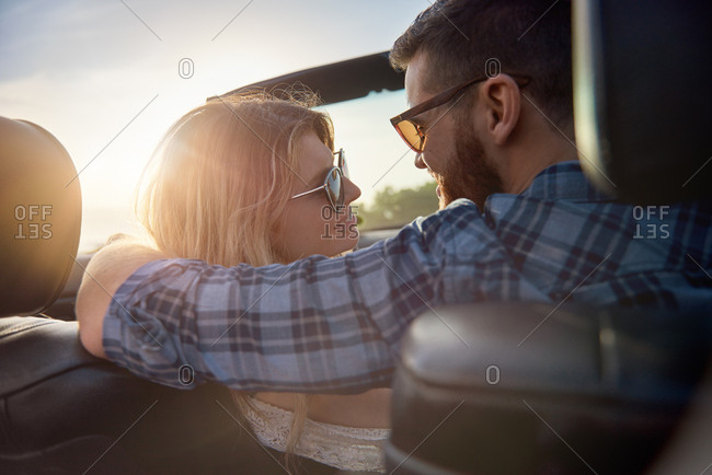 Man puts arm around girlfriend while driving in open top convertible