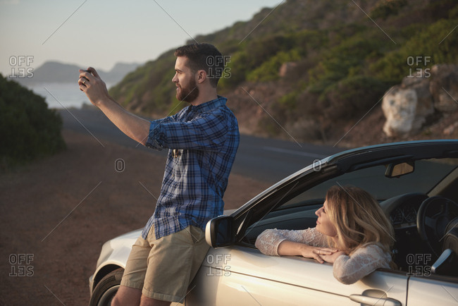 Young beautiful couple in convertible stopping to take photos with mobile cell phone