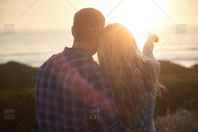 Back view of couple enjoying the sun setting over the horizon