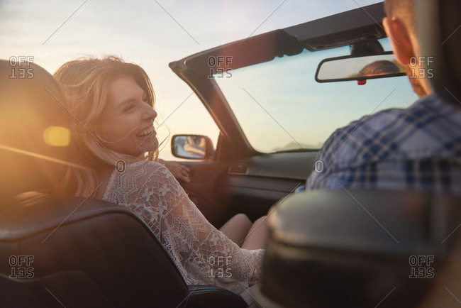 Couple driving in convertible at sunset, girlfriend happy laughing smiling at boyfriend