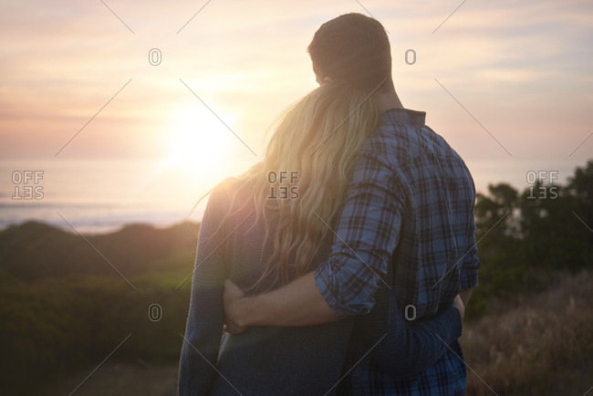 Back view of couple enjoying the sun setting over the horizon,