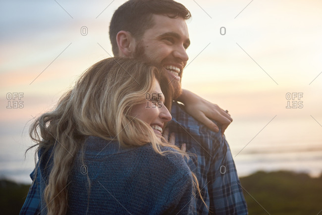 Close up portrait of couple hugging laughing smiling outdoors