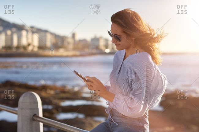 Young beautiful woman texting typing message on cellphone by the sea with sun flare