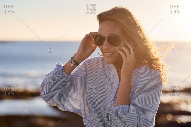 Smiling carefree woman using her mobile cell phone by the ocean at sunset with sun flare