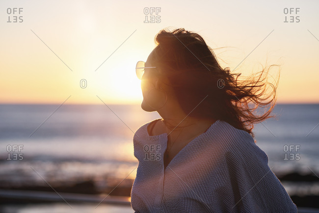 Young happy woman on holiday, enjoying the sun setting into the ocean
