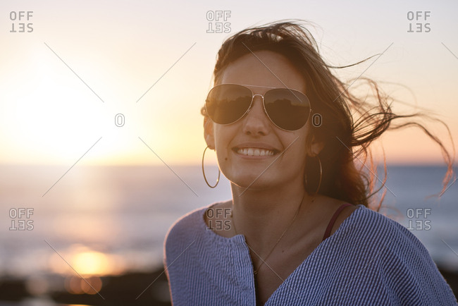 Happy carefree woman smiling with windswept hair by the ocean