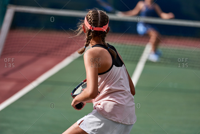Healthy active preteen girl playing tennis on sunny afternoon, returning a shot across the net