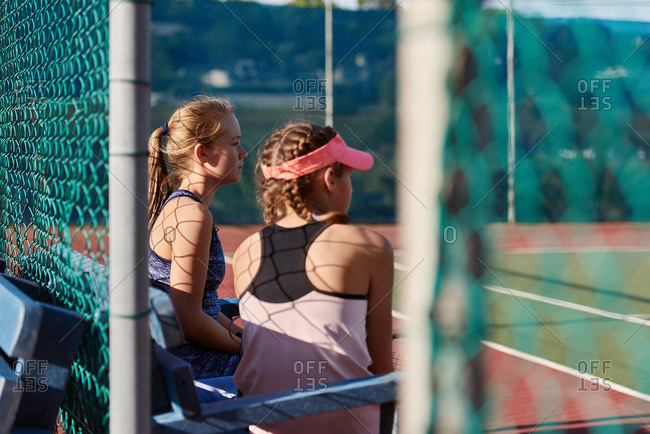 Sporty athletic girls at the tennis courts waiting for their training practice session watching team mates play