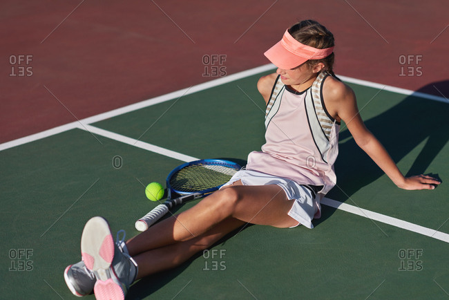Young serious tennis player resting during training session, watching other people playing