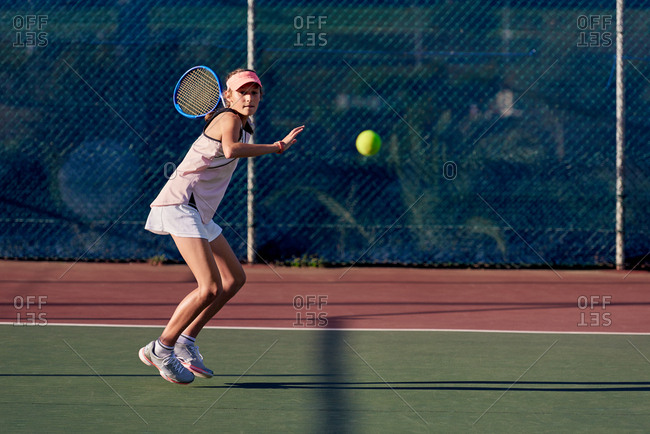Young determined ambitious focused tennis player concentrating on match hitting the ball