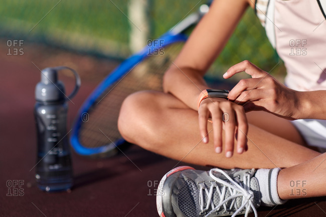 Female tennis player checking her smart watch tracking her activity during training session