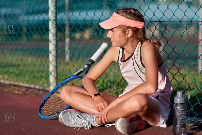 Young serious athlete resting during tennis training, focused determined girl
