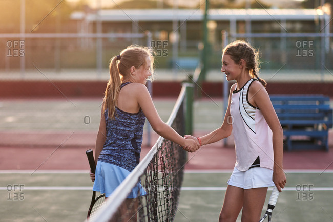 Opponents shake hands after their tennis match game, display of sportsmanship and friendship