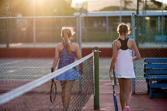Young tennis players finishing their match at end of day