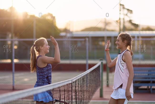 Girls high five after their tennis match tournament competition