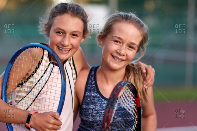 Portrait of pre teen girls smiling while holding tennis rackets, happy ambitious sports players