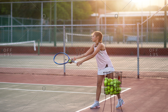 Hardworking tennis player practicing her serve alone, determined and focused athlete