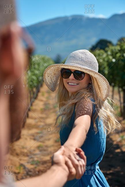 Beautiful woman smiling back at boyfriend walking through vineyard grapevines