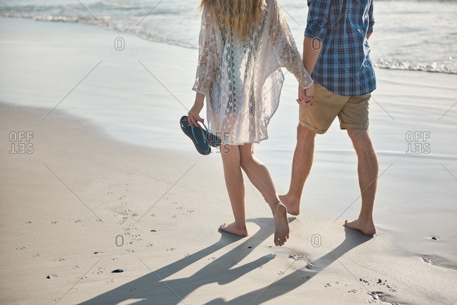 Young couple holding hands walking on empty beach loving hand in hand close relationship