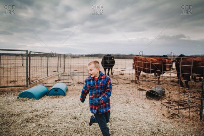 A boy running in a livestock pen