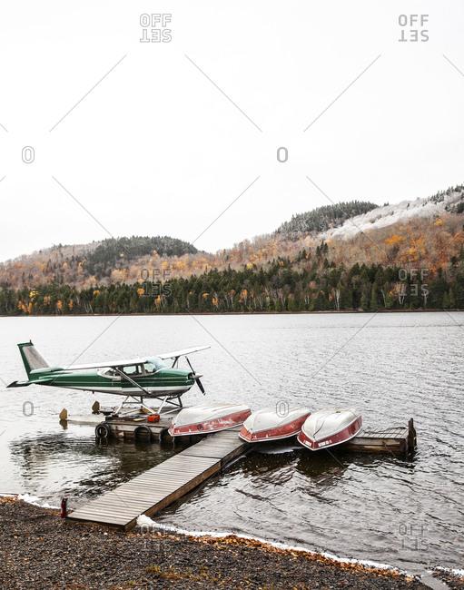 Munsungan Lake, Maine, USA - October 26, 2016: Seaplane at dock with a few rowboats on a lake