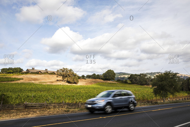 Small SUV speeding by winery and vineyard along highway in Mendocino County